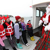 Marblehead: Santa and Mrs. Claus arrive at State Street in Marblehead from a lobster boat hailing from the North Pole as throngs of children gather to greet them. The few lucky children who got to accompany Santa sing carols with Santa and Mrs. Claus on the trip over.  Photo by Liz Curtis