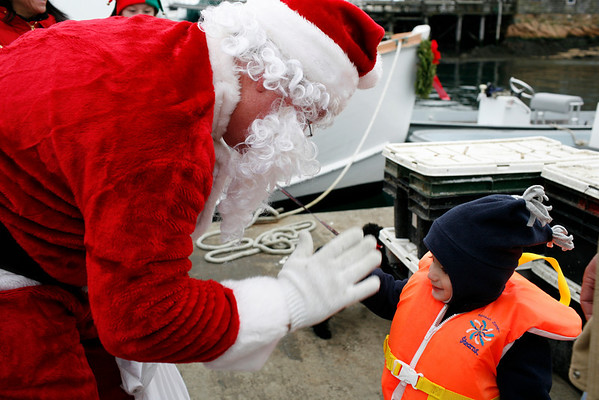 Marblehead: December 5, 2009: Santa and Mrs. Claus arrive at State Street in Marblehead from a lobster boat hailing from the North Pole as throngs of children gather to greet them.  Little Carter Sahagian of Marblehead, whose father is the captain of the boat, gives Santa a high five upon his arrival.  Photo by Liz Curtis