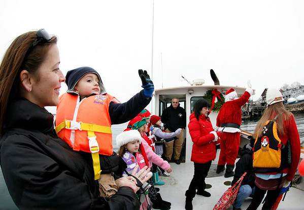 Marblehead: December 5, 2009: Santa and Mrs. Claus arrive at State Street in Marblehead from a lobster boat hailing from the North Pole as throngs of children gather to greet them.  Carter Sahagian, held by his mother Rebecca, waves to greet the crowds. Carter, whose father owns the boat, was lucky enough to catch a ride with Santa.  Photo by Liz Curtis