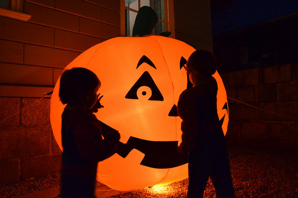 Marblehead: 3-year-old Grey Collins, left, and his brother Griffen, 5, both dressed as spiderman, play with a giant inflated pumpkin.  photo by Mark Teiwes
