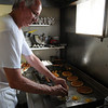 Marblehead:<br /> Kevin O'Malley, one of the cooks, grills up some eggs and pancakes in the kitchen at the Driftwood restaurant.<br /> Photo by Ken Yuszkus/Salem News, Friday August 6, 2010.