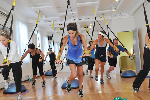 Marblehead: At Energy Within Emily Mitchell of Marblehead, center, leans forward for a triceps workout on TRX suspension systems<br /> photo by Mark Teiwes