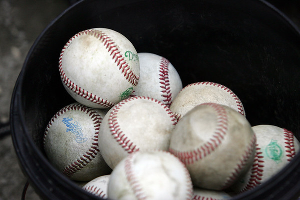 Balls sit in a bucket near a duggout at Gatchell's Park in Marblehead during a little league game between the Twins and the Angels. Photo by Deborah Parker/June 17, 2010