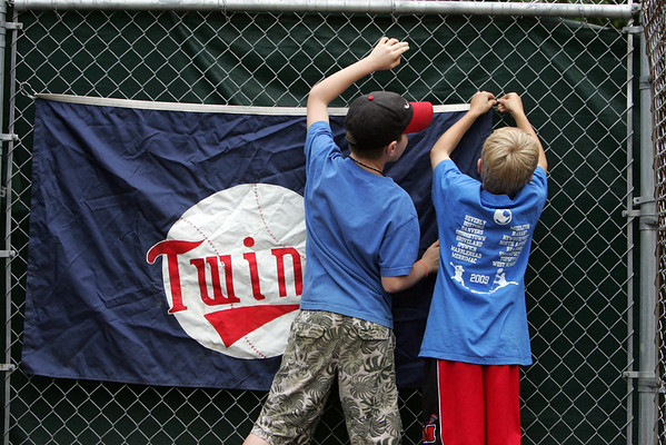 Tom Cronin, 9, and Ben Hutchinson, 9, both of Marblehead hang a sign near the Twin's duggout before the start of a game against the Angels held at Gatchell's Park in Marblehead. Photo by Deborah Parker/June 17, 2010