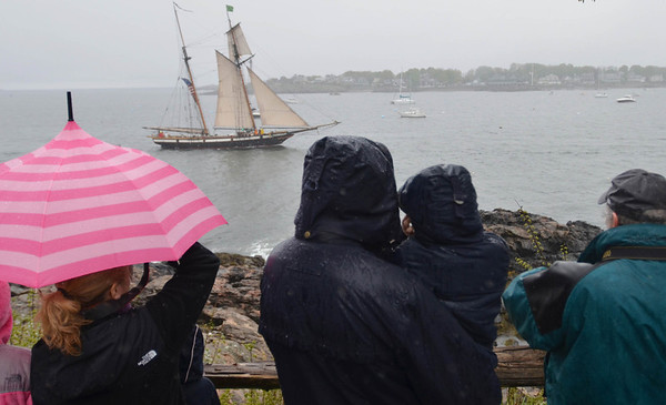 As rain falls, people watch from Fort Sewall the Lynx's arrival in Marblehead Harbor.