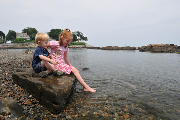 Marblehead:  Hannah Stubbs tests the water with her brother Tyler. photo by Mark Teiwes  Fort beach or Lovis Cove?