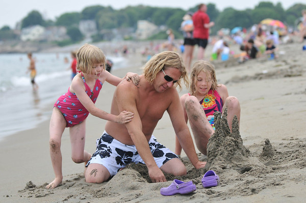 Mablehead: Greg Bates works on a sand castle with his daughters Carly, 7, left, and Madison, 9 at Devereaux Beach. photo by Mark Teiwes