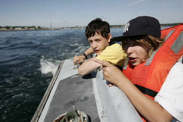 Kirk Clingen, 11, of Marblehead, left, and friend, Hunter Payne, 10, also of Marblehead look over the edge of the boat just before reaching Children's Island where they will spend the day helping to clean up the island after the winter and spring seasons.