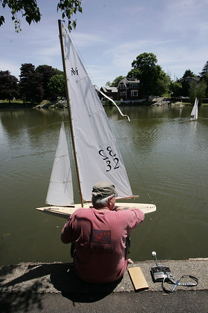 "Nick Laird of Ipswich examines his model yacht in between races held at Redd's Pond in Marblehead. Model Yacht racing has been gong on at Redd's Pond for years. Many people used the Marblehead Class boats, which are now imitated internationally. About 10 years ago, John Snow of Marblehead brought back the old Marblehead Class out of retirement and now many people race those, called ""Vintage Marbleheads."" Photo by Deborah Parker June 13, 2009"