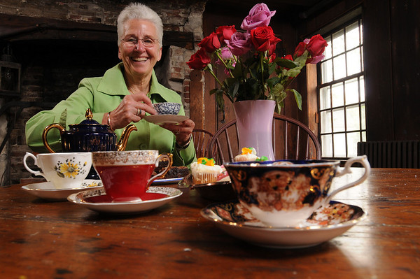 Marblehead:<br /> Lynne Devoe  in the wine cellar of the King Hoope Mansion, at a table with her tea sets<br /> Photo by Ken Yuszkus/Salem News, Friday, May 7, 2010.