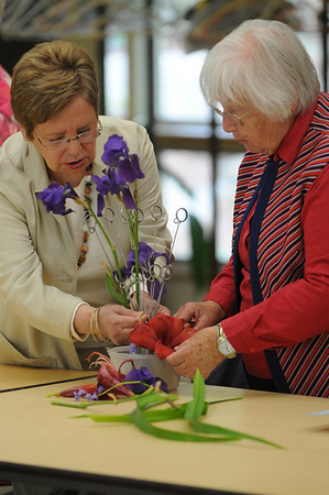 Marblehead:<br /> Sandra Miller, left, and Nancy Graves, both of Marblehead, look over Nancy Graves' floral arrangement at the Arrangers of Marblehead meeting at The Unitarian Universalist Church of Greater Lynn.<br /> Photo by Ken Yuszkus/Salem News, Wednesday, May 12, 2010.