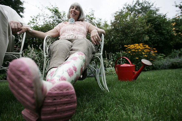 Madelon Bures' sits in her garden with her signiature gardening boots and red water pale.  Photo by Deborah Parker/August 13, 2009