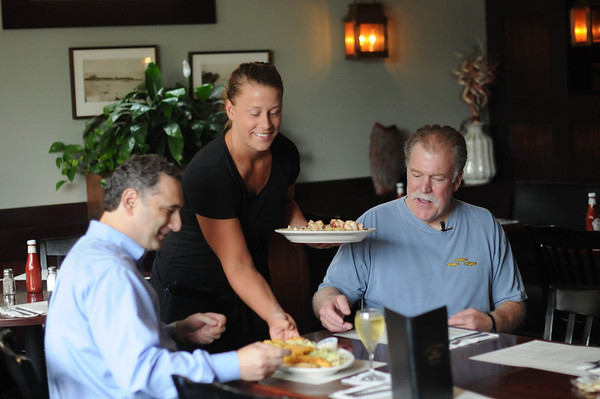 Three Cods Tavern waitress Amanda Roland serves Robert Simonelli, left, and Chip Percy during a taping of the show.