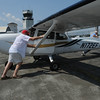 Marblehead and Beverly Airport:<br /> Don Humphreys, 87,in red hat, of Marblehead has renewed his pilot's license and is flying again after a 45-year lapse. He is moving the plane  with flight instructor, Dennis Silverio back the plane into its parking spot after their flight over Marblehead.<br /> Photo by Ken Yuszkus/Salem News, Tuesday, August 2, 2011.