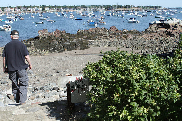 Dennis Curtin makes his way down to the beach at a right of way at the end of Harvard Street on Marblehead Neck.