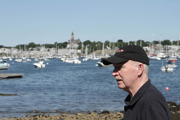 Dennis Curtin walks along the beach at a right of way at the end of Harvard Street on Marblehead Neck.