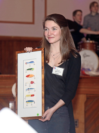 DAVID LE/Staff photo. Volunteer Grace MacDonald holds up an item for auction at the annual Marblehead Festival of Arts auction night held at Abbott Hall on Saturday April, 9, 2016. 4/8/16.