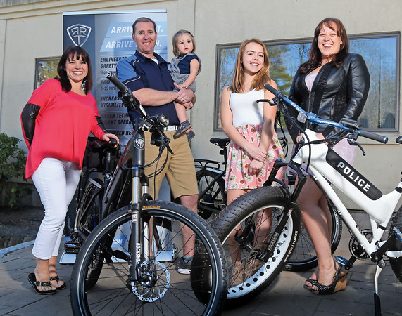 DAVID LE/Staff photo. Adam Rand, of Marblehead, is a maker of electric bikes that are being distributed and used by many local law enforcement patrol units including in town at the Marblehead Police Department. Rand holds his sixteen-month old daughter, Dagny, while standing with his wife, Jessica, left, step-daughter Brianna Moore, 14, second from right, and employee Samantha Barnes. 4/21/16.
