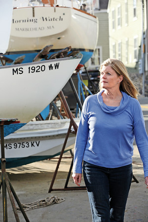 KEN YUSZKUS/Staff photo.      Susan Cairns Fischer, who has written two books of boat names and the stories behind them, walks amongst the boats in Marblehead.    05/10/16