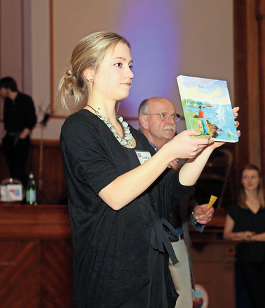 DAVID LE/Staff photo. Volunteer Cordelia Roberts holds up a painting for auction at the annual Marblehead Festival of Arts auction night held at Abbott Hall on Saturday April, 9, 2016. 4/8/16.
