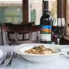 The Porcini Pappardelle from Casa Mia Cucina Italiana is a healthy portion of pappardelle pasta and mushrooms in a white wine garlic sauce and topped with parsley and is pictured here with a bottle of red wine.