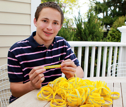 "Marblehead: Thirteen-year-old Cole Garaventi, a student at Marblehead Veterans Middle School, sold bracelets to donate money to One Fun Boston after the Boston Marathon Bombing on April 15th, 2013. Garaventi ordered 5,000 blue and yellow bracelets with the inscription ""Pray for Boston"" and ""April 15, 2013"" on them and has raised over $10,000 over a three week span. Garaventi was sent an autographed picture from Boston Red Sox third baseman Will Middlebrooks after the Sox star heard of Garaventi's efforts to help the One Fund. David Le/Marblehead Home & Style"