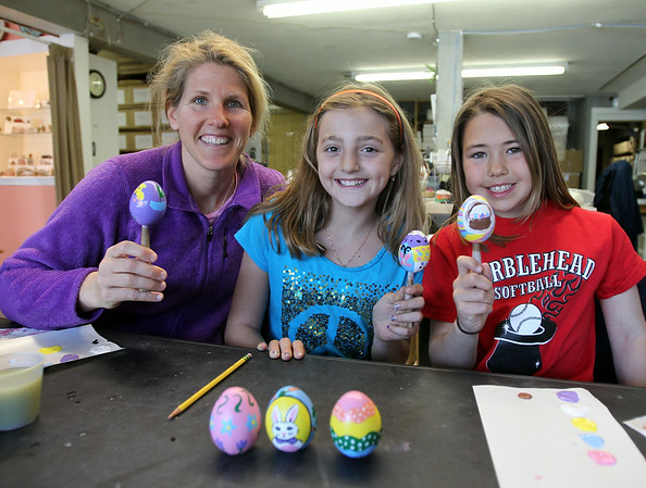 From left: Kristin Goedkoop, Sophia Ianchulev, 9, and Eloise Goedkoop, 8, all of Marblehead, show off ceramic Easter eggs they painted at Hestia Creations during Marblehead's Spring Fling on Saturday afternoon. DAVID LE/Staff photo. 4/12/14