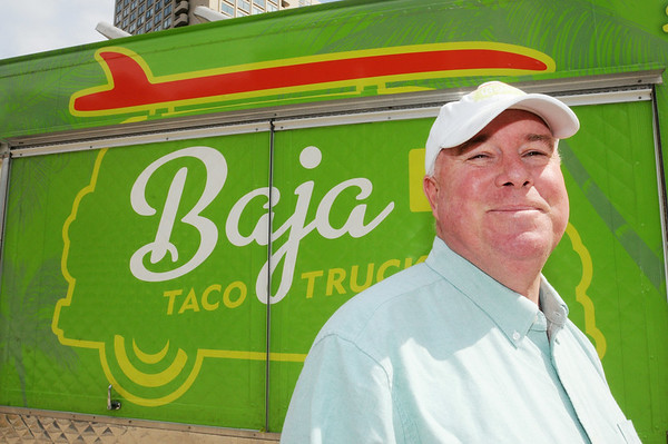 KEN YUSZKUS/Staff photo.  Bryan Peugh of Marblehead owns and operates one of the estimated 70 food trucks in Boston. His is a Mexican food truck called Baja Taco Truck. His truck is near Rowe's Wharf in Boston at noontime on a Friday.