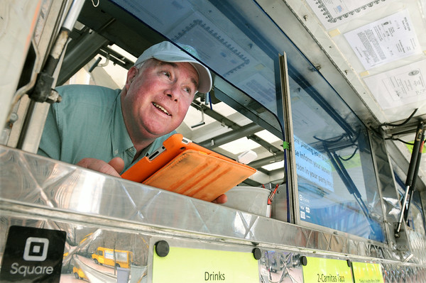 KEN YUSZKUS/Staff photo.  Bryan Peugh of Marblehead owns and operates one of the estimated 70 food trucks in Boston speaks with a customer. His is a Mexican food truck called Baja Taco Truck. His truck is near Rowe's Wharf in Boston at noontime on a Friday.