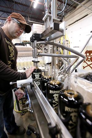 KEN YUSZKUS/Staff photo.  President Eric Glass at Pirate Dog Brand LLC in Salem, maker of Rumson's Rum, fills bottles of coffee flavored rum.     5/12/15
