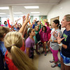 KEN YUSZKUS/Staff photo.  Far right, Fit Girls Run Club of Marblehead coach Mandy Murphy speaks to the girls just before they all go outside for a run around the track at the Village School in the rain. To the left of her is coach Annie Pugh.   10/16/14