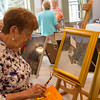 JOE DIFAZIO/ Martha Fucarile of Middleton browses throughout some of the paintings at Middleton Art Association's annual art fair at the Middleton Historical Society. May 14, 2016