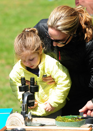 JIM VAIKNORAS/Staff photo Amanda Kosinski gives her daughter Abby, 3, a boost so she can use a microscope during their 100th Birthday party Saturday. Almost 700 people attended the event enjoying cake , hot dogs, games, fishing, and programs to learn about the history of the forest.