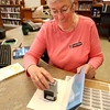 KEN YUSZKUS/Staff photo.      Circulation's Claudia Johnson hand stamps an outgoing book at Middleton's Flint Public Library .    05/18/16
