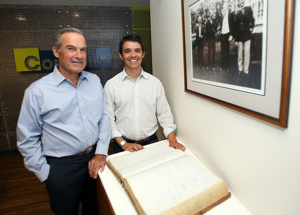 Father and son tandem Steve, left, and Jay Connolly, of Marblehead, are the 4th and 5th generations of their family to run their family business, Connolly Brothers Construction and Development, of Beverly. The Connolly's stand in front of an old photograph of the founding members of the company and an accounting ledger from the early 1900's on display in their office located at 152 Conant Street. DAVID LE/Staff photo. 8/20/14.