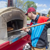 Joe Difazio/ Travis Wojcik of Peabody pulling a pizza out of a mobile oven at the Family Festival at Brooksby Farm in Peabody. May 15, 2016