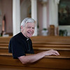 Father John MacInnis poses for a photo inside St. John's church in Peabody. Photo by Mary Schwalm