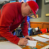 PARKER FISH/Photo. Scott Connolly places a bid in the silent auction during the Pints for Pete fundraiser at Champions Pub in Peabody 5/5/16