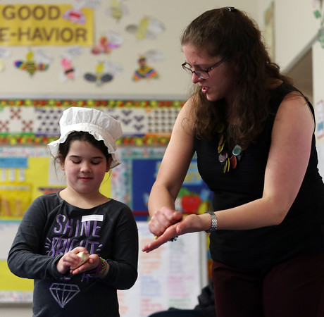 DAVID LE/Staff photo. South Memorial School second grader Avery Skinner makes a scrubbing motion while pretending to wash clothes while acting the part of Sarah Revere, daughter of Paul Revere, during a re-enacting of Paul Revere's ride, with Emily Holmes of the Paul Revere House. 3/16/16.