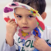 KEN YUSZKUS/Staff photo.     Anthony Jacobsen, 3, finds a unique way to use the spring wreath that he made during the Mother Goose Story Time at the Peabody Institute Library South Branch.      04/12/16