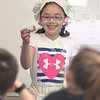 DAVID LE/Staff photo. South Memorial School second grader Isabella Santana laughs while holding up a long spool of thread while acting the part of Rachel Revere, wife of famed Paul Revere during a re-enacting of Paul Revere's ride, with Emily Holmes of the Paul Revere House. 3/16/16.