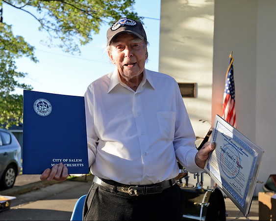 RYAN HUTTON/ Staff photo<br /> 99-year-old trumpeter Frank Higgins, holds up the pair of commendations he received for his years of playing with the North Shore Concert Band before their season opener show at the Robert Hayes Bandshell at Salem Willows on Thursday night.