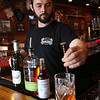 KEN YUSZKUS/Staff photo.          The Village Tavern's bartender Evan Johnson makes a Sazerac cocktail.          05/04/16