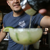 KEN YUSZKUS/Staff photo.   Howling Wolf bartender Rico Alas pours out the finished jalapeno martini into a glass.      05/03/16