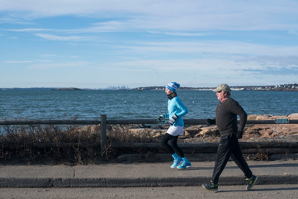 """SAM GORESH/Staff photo. Wicked Run Club members Kendra Burke and Stephen McWhirter run along Ocean Avenue in Marblehead during the """"No Rest for the Wicked"""" Saturday morning run. 1/28/17"""