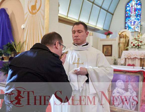 Szymon Bieganski kisses the relic of St. John Paul II's held by Father Robert Bendzinski at John Paul II Divine Mercy Shrine in Salem, Sunday, April 8, 2018. Jared Charney / Photography