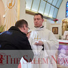 Szymon Bieganski kisses the relic of St. John Paul II's held by Father Robert Bendzinski at John Paul II Divine Mercy Shrine in Salem, Sunday, April 8, 2018. Jared Charney / Photography