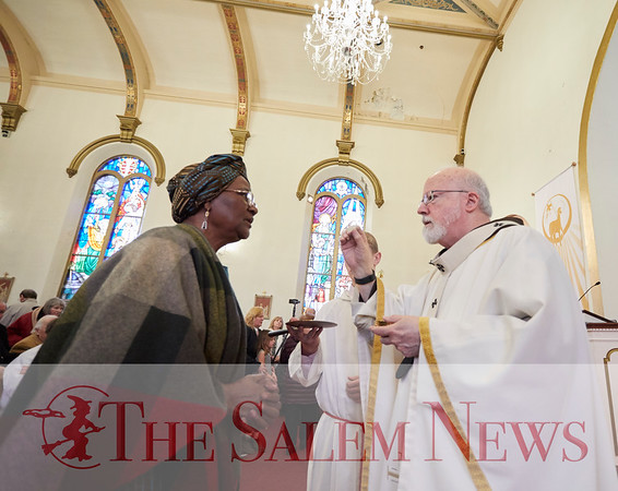 Cardinal Sean O'Malley gives Crescence Go Manyo communion at the presentation of St. John Paul II's relic at John Paul II Divine Mercy Shrine in Salem, Sunday, April 8, 2018. Jared Charney / Photography