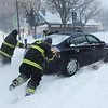PAUL BILODEAU/Staff photo. A group of firefighters help fellow firefighter Dan Blanchette get free after he got stuck near the back of the fire station on Klop Alley during the morning hours of the blizzard of 2015.