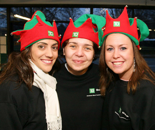 TD Bank volunteers who assisted at the race, from left, Rhiannon Schiavone, Ana Pantazi, both<br /> of Andover and Jacki Dion of North Andover,<br /> at the Feaster Five Road Race, Thanksgiving morning, Shawsheen Square in Andover.<br /> 11-26-09                         Photo by Frank J. Leone, Jr.
